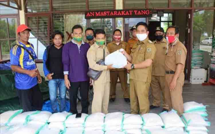 Camat Kamipang Ade Irwan secara simbolis menyerahkan paket sembako kepada kepala desa untuk didistribusikan ke masyarakat terdampak banjir.