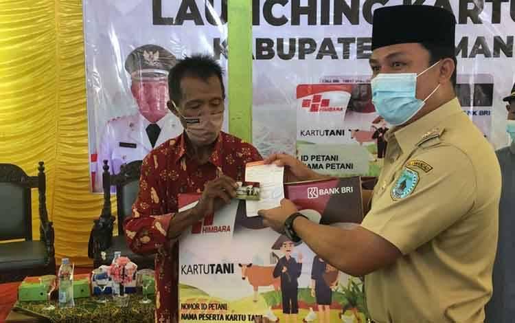 Bupati Lamandau, Hendra Lesmana menyerahkan Kartu Tani kepada perwakilan petani di Desa Tri Tunggal, Sematu Jaya, Selasa 29 September 2020