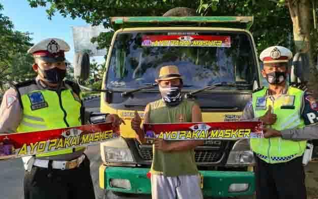 Anggota Ditlantas Polda Kalteng saat memasang stiker 'Ayo Pakai Masker' di truk angkutan.