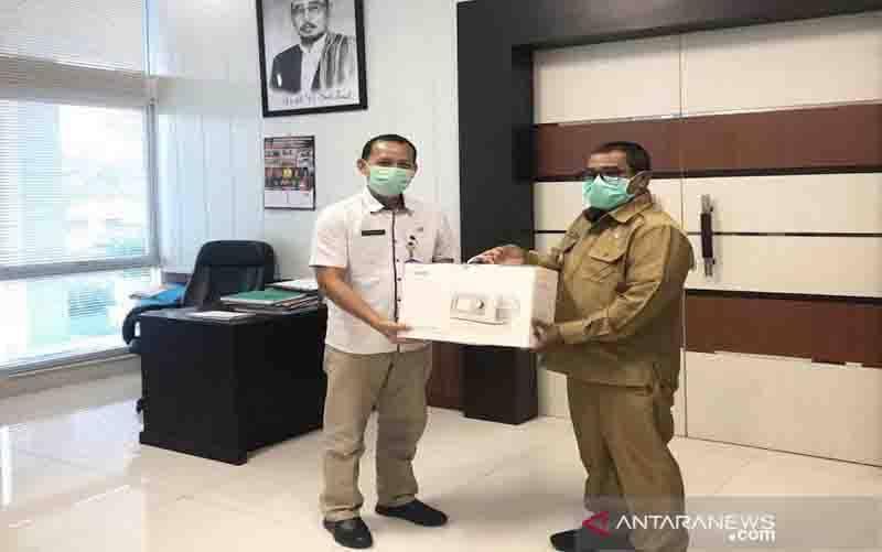 Pelaksana Tugas Gubernur Kalteng Habib Ismail bin Yahya (kanan) menyerahan ventilator mobile secara simbolis kepada Juru Bicara Gugus Tugas Penanganan COVID-19 Barito Utara Siswandoyo di Palangka Raya, Selasa (29/9/2020). (foto : ANTARA/HO)