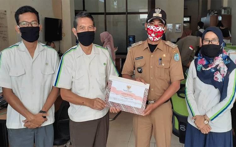 Kepala Desa Mekarmulya,Herlangga Tri Atmaja SH (dua kanan) memberikan penghargaan kepada PT Sawit Sumbermas Sarana Tbk diterima oleh Kepala Departemen CSR, Kharis Nuryanto (dua kiri).