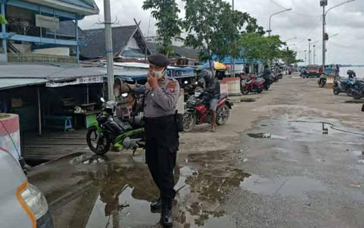 Personel Satbinmas Polres Kapuas saat memberikan imbauan protokol kesehatan di kawasan pelabuhan Danau Mare Kuala Kapuas.