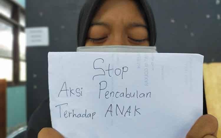 Seorang perempuan memegang tulisan stop aksi pencabulan terhadap anak. Sementara, pelaku pencabulan anak 9 tahun di Kecamatan Pulau Hanaut terancam 15 tahun penjara.