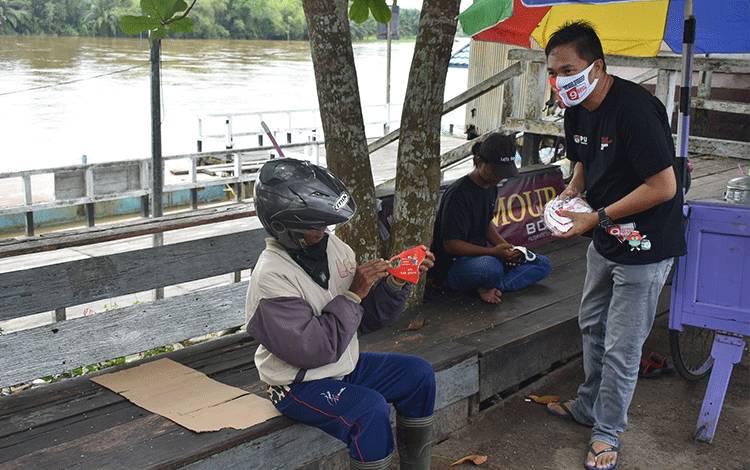 Komisioner KPU Seruyan saat menyampaikan sosialisasi sekaligus memberikan masker kepada salah seorang warga Pembuang Hulu.