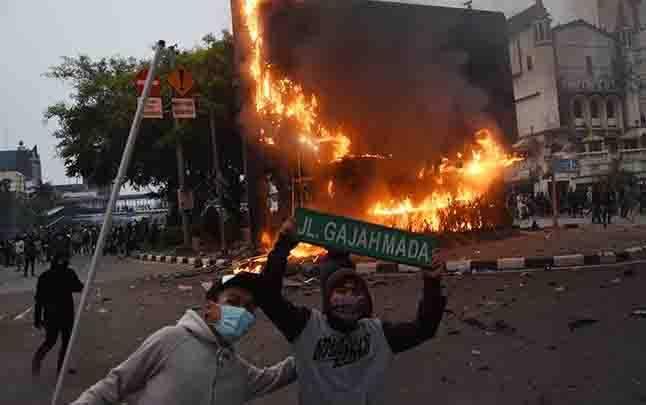 Sebuah pos polisi dibakar pengunjuk rasa yang menolak pengesahan Omnibus Law UU Cipta Kerja saat bentrok dengan polisi di kawasan Harmoni, Jakarta, Kamis 8 Oktober 2020. Unjuk rasa tersebut berakhir ricuh dan mengakibatkan sejumlah fasilitas umum rusak. (foto : ANTARA FOTO/Indrianto Eko Suwarso)