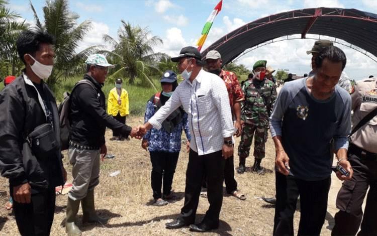 Wakil Ketua DPRD Kotawaringin Timur, H Rudianur (baju putih) saat mendatangi petani di Desa Lampuyang saat panen.