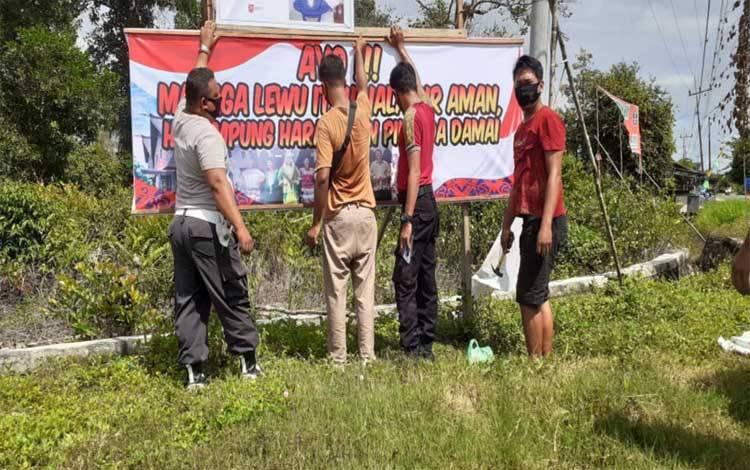 Anggota Polsek Katingam Hilir memasang spanduk imbauan jelang Pilgub Kalteng