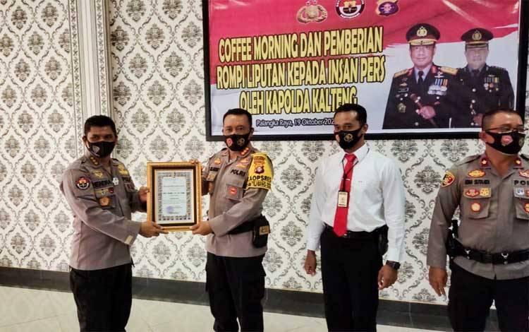 Kabid Humas Polda Kalteng Kombes Hendra Rochmawan menyerahkan penghargaan kepada Kapolresta Palangka Raya Kombes Dwi Tunggal Jaladri, Senin 19 Oktober 2020
