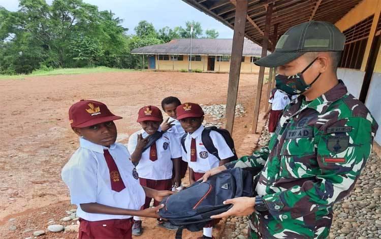 Prajurit TNI memberikan tas baru kepada anak-anak Papua