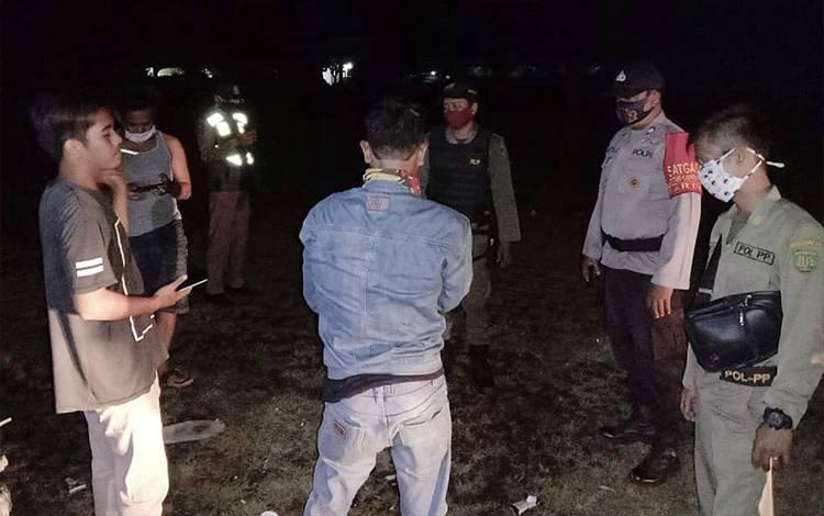 Personel Polsek Dusun Tengah dan Satpol PP melakukan patroli cipta kondisi pada malam hari.