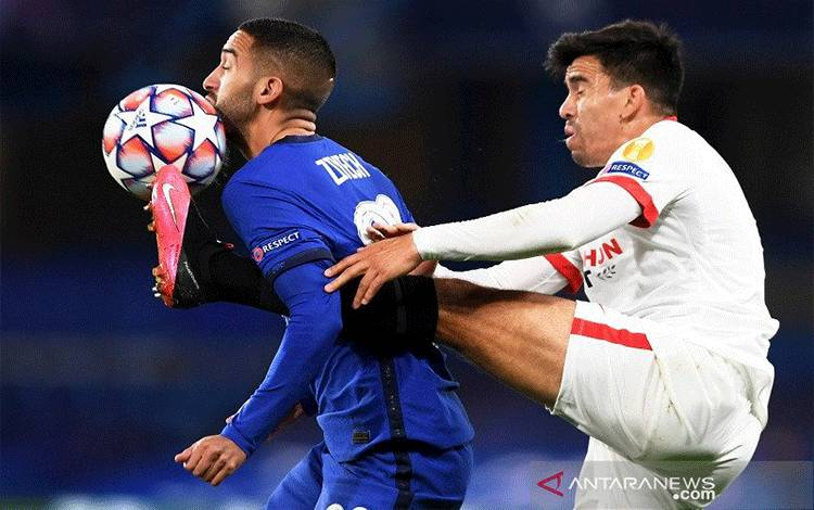 Bek Sevilla Marcos Acuna (kanan) berusaha merebut bola dari penguasaan penyerang sayap Chelsea Hakim Ziyech dalam penyisihan Grup E Liga Champions di Stadion Stamford Bridge, London, Inggris, Selasa (20/10/2020) waktu setempat. (ANTARA/REUTERS/POOL/Mike Hewitt)