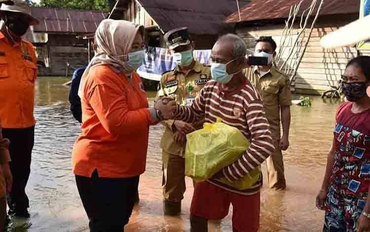 Bupati Kobar Hj Nurhidayah saat meninjau dan menyerahkan bantuan kepada warga terdampak banjir di Aruta.