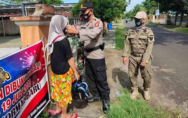Kapolsek Seruyan Hilir, AKP Setiyono memasangkan masker kepada salah satu warga sambil memberikan edukasi terkait protokol kesehatan, Rabu, 21 Oktober 2020.