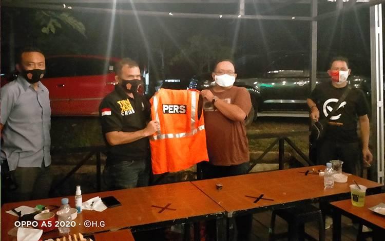 Kapolres Gunung Mas  AKBP Rudi Asriman menyerahkan secara simbolis rompi pers kepada Ketua PWI Popy Oktovery saat ngopi bareng di Kedai Pras Kopi Jalan Ledjend Soeprapto, Kuala Kurun, Rabu malam, 21 Oktober 2020.
