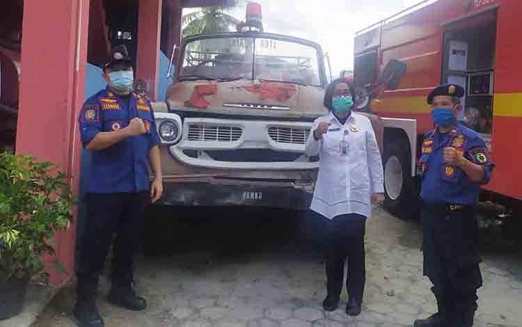 Kepala Dinas Damkar dan Penyelamatan Kota Palangka Raya Gloriana Aden bersama anggota foto di mobil tua