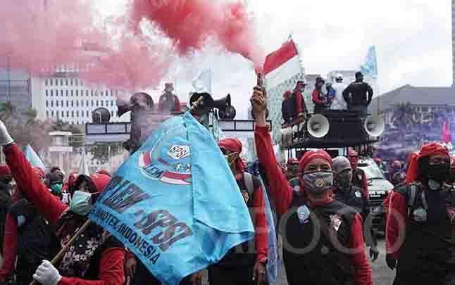 Sejumlah buruh menyalakn flare saat melakukan aksi di Jalan MH Thamrin, Jakarta, Kamis, 22 Oktober 2020. (foto : TEMPO/Muhammad Hidayat)