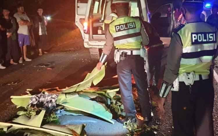 Sejumlah aparat kepolisian saat hendak mengevakuasi korban kecelakaan meninggal dunia.