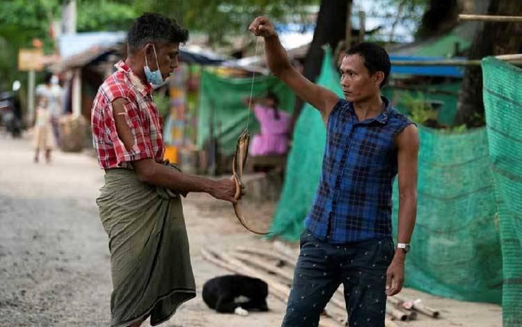Seorang pria menjual belut selama lockdown untuk memperlambat penyebaran infeksi virus corona di daerah kumuh Yangon, Myanmar, 21 Oktober 2020. [REUTERS / Shwe Paw Mya Tin]