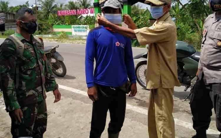 Kades Bangun Harja, Mahmud Hasani memakaikan masker kepada warga sambil memberikan imbauan agar selalu taati protokol kesehatan