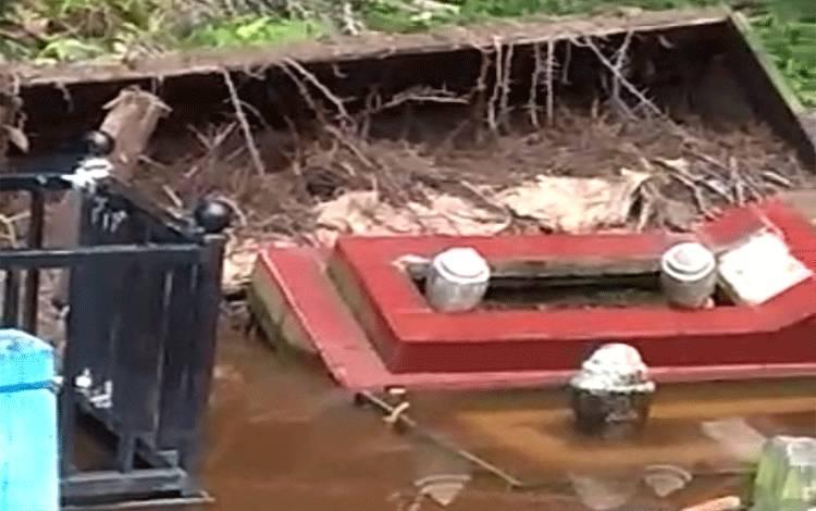 Kondisi kuburan yang terbongkar akibat pohon kelapa sawit tumbang.