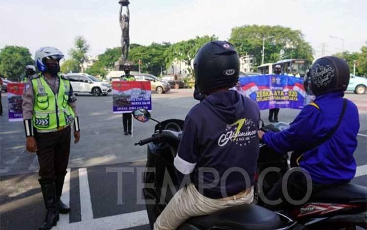 Petugas kepolisian saat mensosialisasikan Operasi Zebra di Bundaran Senayan, Jakarta Pusat, Rabu pagi 28 Oktober 2020. TEMPO/M Julnis Firmansyah