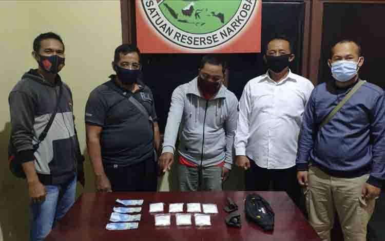 Tersangka pengedar pil koplo Bah (41) diapit anggota Polres Katingan saat menujukkan barang bukti/