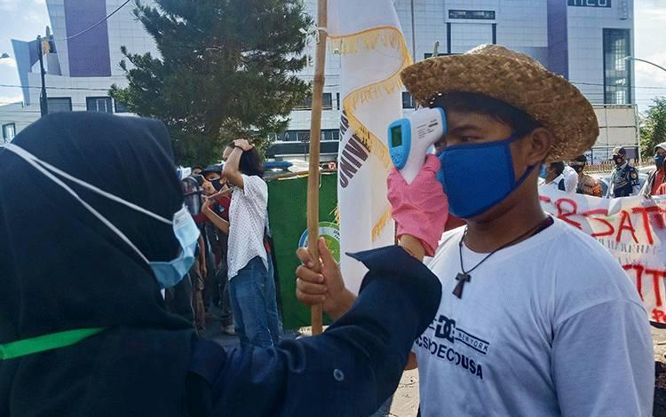 Para mahasiswa saat dilakukan pengecekan suhu tubuh oleh petugas.