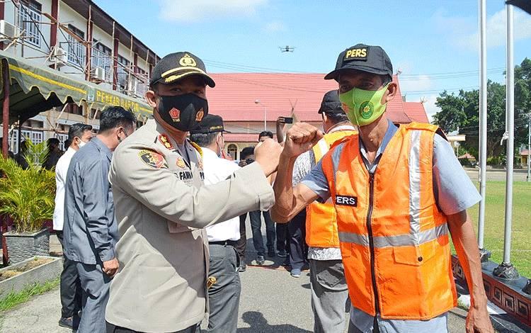 Kapolres Barito Timur AKBP Affandi Eka Putra membagikan rompi dan topi kepada wartawan.