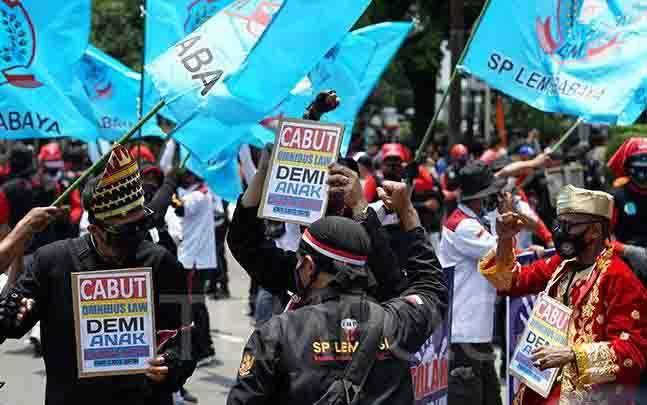 Peserta membawa poster berisi pesan menolak omnibus law saat melakukan aksi di Kawasan Patung Arjuna Wijaya, Jakarta, 28 Oktober 2020. Dalam aksi tersebut para buruh menuntut pembatalan pengesahan UU Cipta Kerja Omnibus Law. (foto : TEMPO/Muhammad Hidayat)