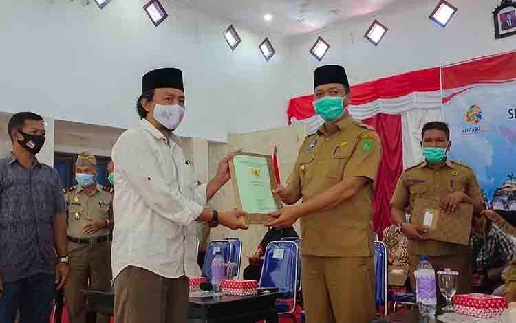 Bupati Sukamara, Windu Subagio menyerahkan sertifikat program PTSL kepada masyarakat