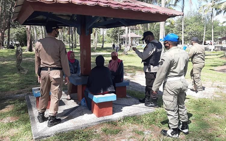 Satgas yustisi Covid-19 saat mengigatkan pengunjung Pantai Sungai Bakau agar disiplin menerapkan protokol kesehatan.