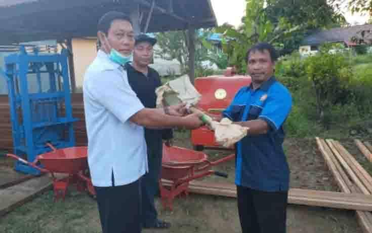 Kepala Dinas Sosial Kabupaten Gunung Mas, Jhonson Ahmad (baju putih) disaksikan Lurah Tampang Tumbang Anjir Berjoaldi menyalurkan bantuan kepada Karang Taruna Sumber Harapan, baru-baru ini.