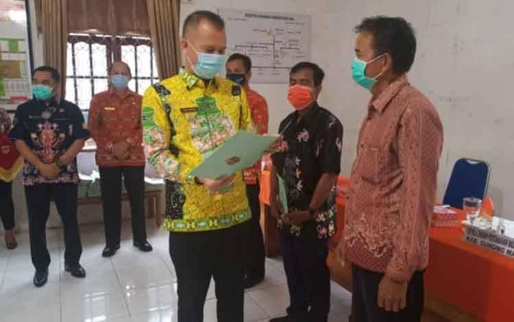 Bupati Gunung Mas, Jaya Samaya Monong menyerahkan sertigikat kepada warga
