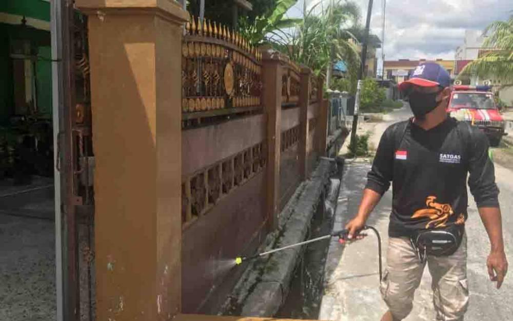 Personel Satgas Covid-19 Palangka Raya menyemprotkan disinfektan di kawasan permukiman warga.