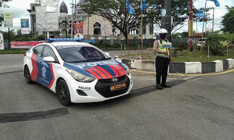 Anggota Satlantas Polresta Palangka Raya mengatur arus lalu lintas sambil mengingatkan disiplin protokol kesehatan cegah covid-19.