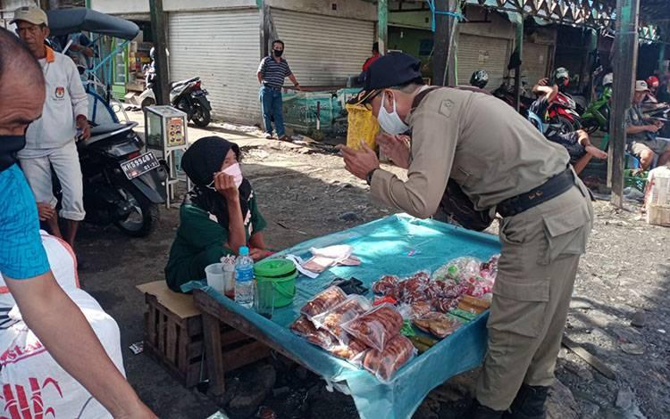 Personel Satpol PP dan Damkar Kapuas imbau pedagang di pasar terapkan protokol kesehatan.