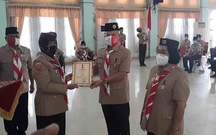 Waka Sekretaris Kwarda Gerakan Pramuka Kalimantan Tengah, Norhani menyerahkan piagam penghargaan kepada Kamabicab Gerakan Pramuka Gumas, Jaya S Monong.