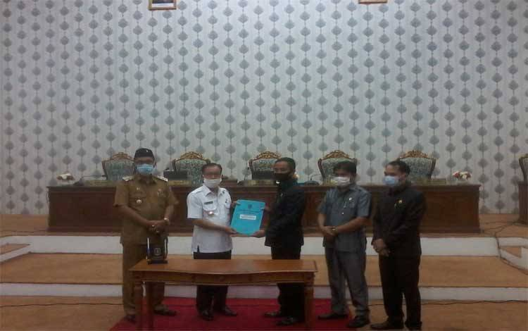 Ketua DPRD Katingan, Marwan Susanto menyerahkan dokumen RAPBD 2021 kepada Bupati Sakariyas setelah penandanganan persetujuan bersama