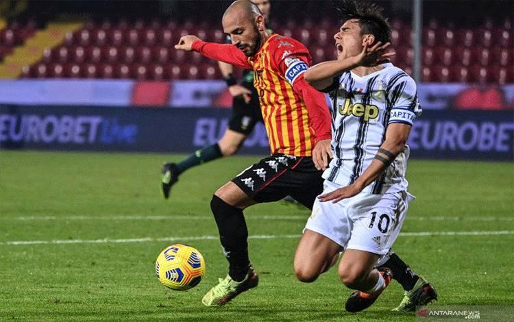 Bek Benevento Luca Caldirola (kiri) melanggar penyerang Juventus Paulo Dybala pada pertandingan Liga Italia yang dimainkan di Stadio Ciro Vigorito, Benevento, Sabtu (28/11/2020). (ANTARA/AFP/ALBERTO PIZZOLI)
