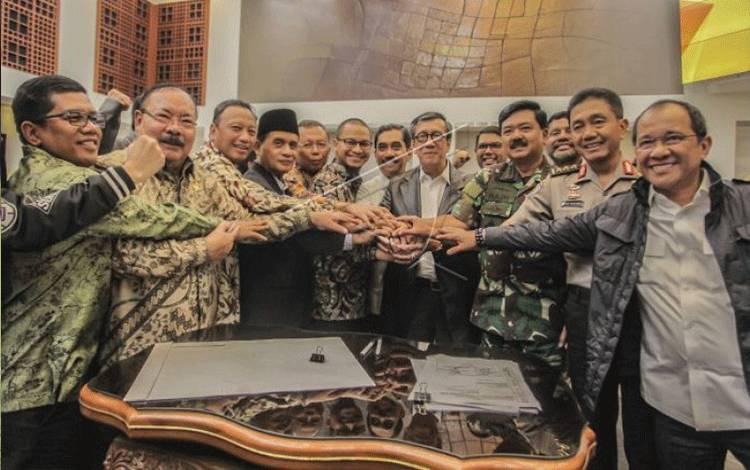 Menkumham Yasonna Laoly (keenam kanan) berjabat tangan bersama Ketua Pansus Terorisme Muhammad Syafii (keempat kiri), Panglima TNI Marsekal Hadi Tjahjanto (ketiga kanan), Irwasum Polri Komjen Pol Putut Eko Bayuseno (kedua kanan), Kepala BNPT Komjen Pol Suhardi Alius (ketujuh kiri) dan Anggota Pansus Terorisme DPR lainnya usai ditandatanganinya hasil revisi UU Anti-Terorisme pada Rapat Kerja Penetapan Revisi UU Anti-Terorisme di Kompleks Parlemen Senayan, Jakarta, Kamis (24/5). (ANTARA FOTO/Muha