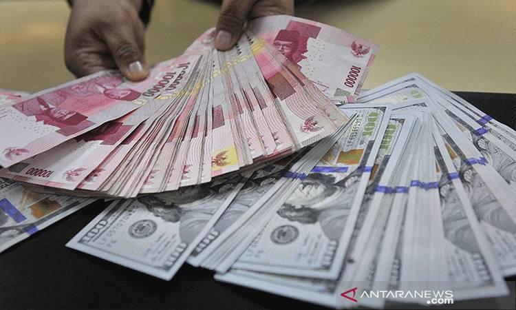 Seorang teller sebuah bank merapikan lembaran mata uang rupiah dan dolar Amerika di Jakarta. ANTARA FOTO/Puspa Perwitasari/am.