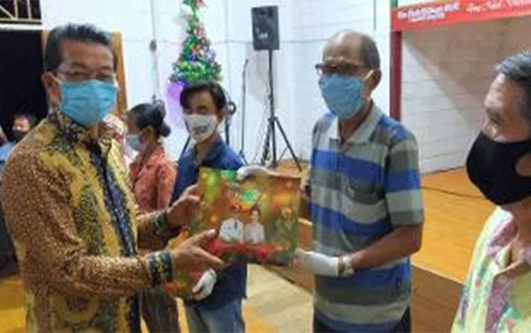 Bupati Murung Raya Perdie MYoseph menyerahkan bingkisan Natal kepada masyarakat Desa Kalang Kaluh Kecamatan Tanah Siang.
