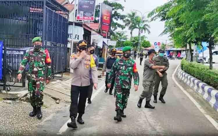 Tim gugus tugas disiplin Covid-19 saat melakukan patroli sekaligus membagikan masker kepada masyarakat, Rabu 2 Desember 2020.