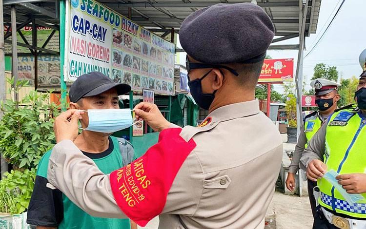 Petugas saat memberikan dan memasangkan masker baru kepada pengendara yang terjaring razia di Jalan G Obos Palangka Raya pada Rabu, 2 Desember 2020.