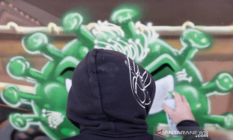 """Seniman David """"S.I.D."""" Perez melukis grafiti, menggambarkan dua vaksin (Modernos 19 dan Pizter Klorokinos) untuk mencegah infeksi virus di belakang gim video populer Street Fighter di Gland, Swiss, Kamis (3/12/2020), di tengah mewabahnya infeksi virus corona (COVID-19) . REUTERS/Denis Balibouse/AWW/djo"""