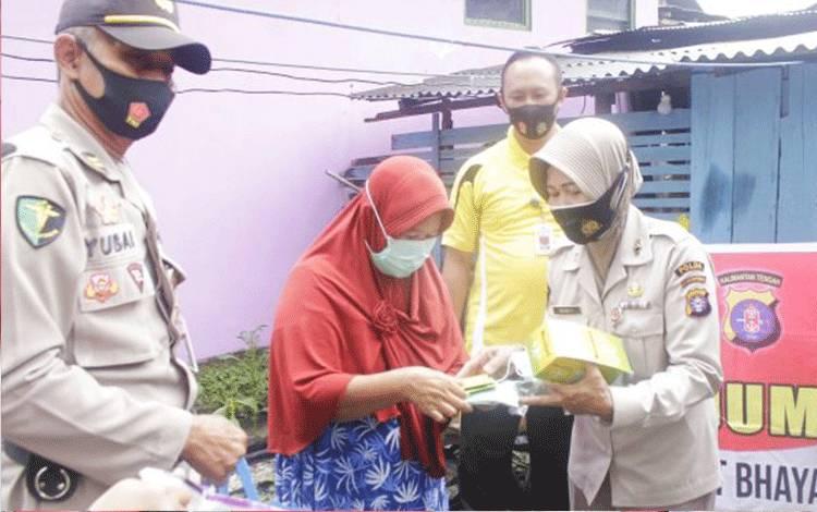Personel RS Bhayangkara tingkat III Palangka Raya membagikan paket sembako, masker dan vitamin kepada salah satu warga.