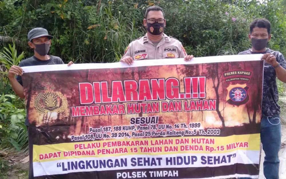 Anggota Polsek Timpah saat mengajak warga cegah terjadinya karhutla di wilayah Kecamatan Timpah.