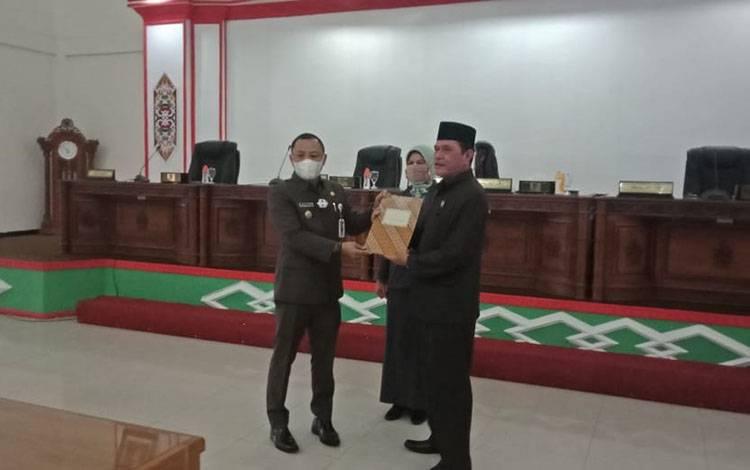 Wakil ketua I DPRD Barsel didampingi waketII menyerahkan persetujuan bersama kepada Bupati Barsel