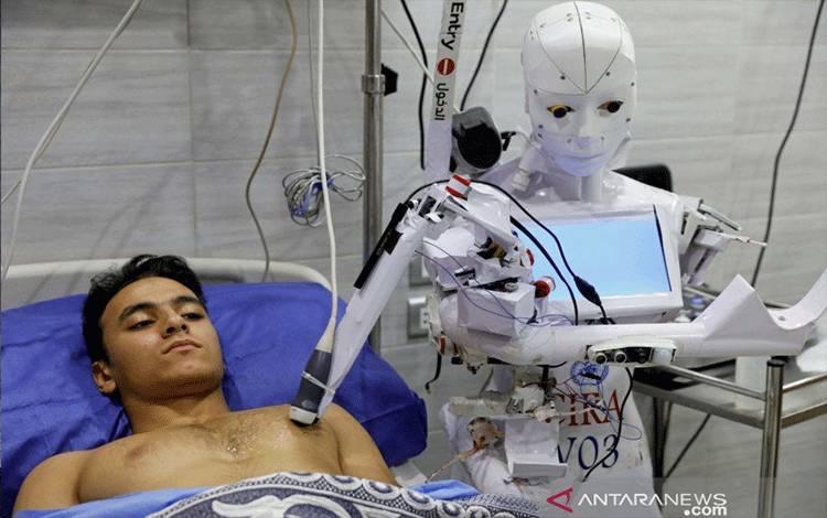 Seorang sukarelawan di Tanta, Mesir, Rabu (18/11/2020), diperiksa oleh Cira 3, robot yang dikendalikan dari jarak jauh untuk melakukan tes terhadap terduga pasien dengan penyakit virus corona (COVID-19) untuk membatasi paparan manusia terhadap virus, di tengah gelombang kedua infeksi . REUTERS/Mohamed Abd El Ghany/hp/cfo