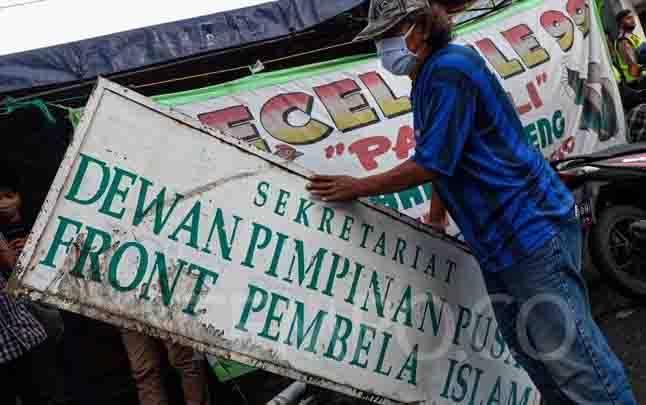 Plang Front Pembela Islam (FPI) dicopot pasca pemerintah resmi membubarkan FPI, di Petamburan, Jakarta, Rabu, 30 Desember 2020. Aparat kepolisian tampak mencopoti baliho bertuliskan FPI maupun yang bergambar Rizieq Shihab di kawasan Petamburan yang merupakan markas FPI. (foto : TEMPO/Hilman Fathurrahman W)
